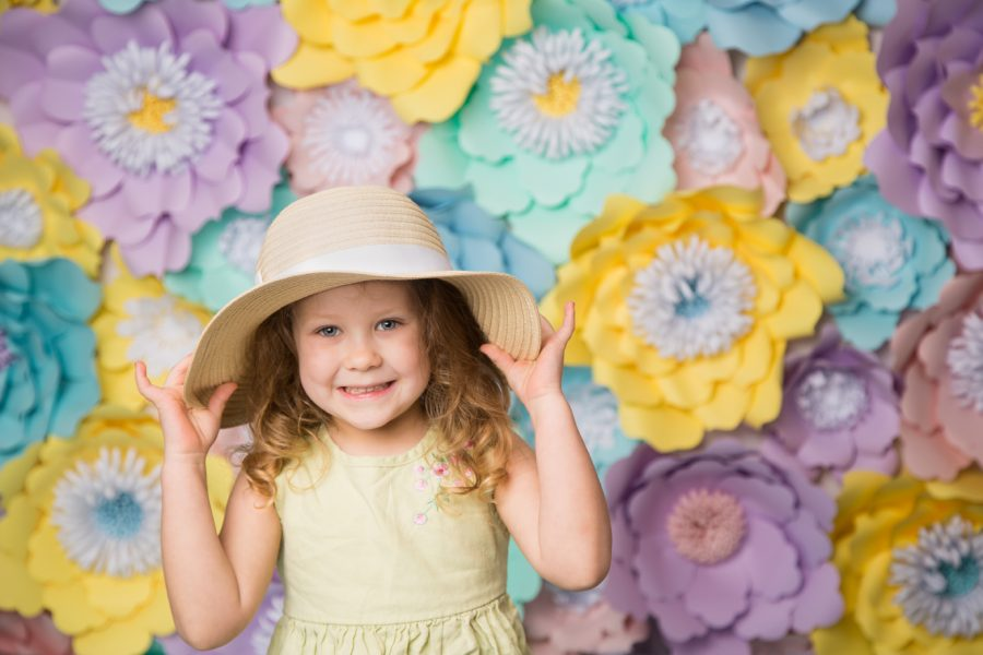 girl in sunhat in front of flower background